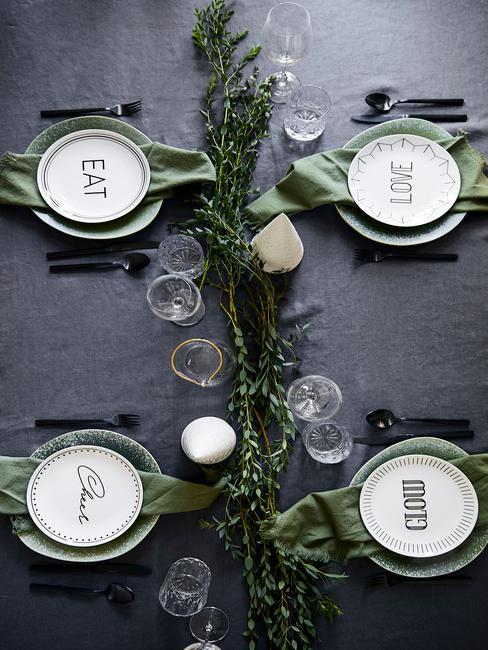 Stół przykryty ancracytowym obrusem, udekorowany gałązką świerku, zastawą Westwing oraz srerbnymi sztućcami