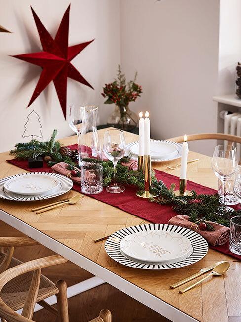Drewniany sół z czerwonym bieżnikiem, czarno-białymi talerzami, gałązką świerku i złotym świecznikiem
