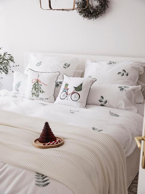 Zbliżenie na łóżko z białą świąteczną pościelą z poduszkami z motywem jemioły i roweru