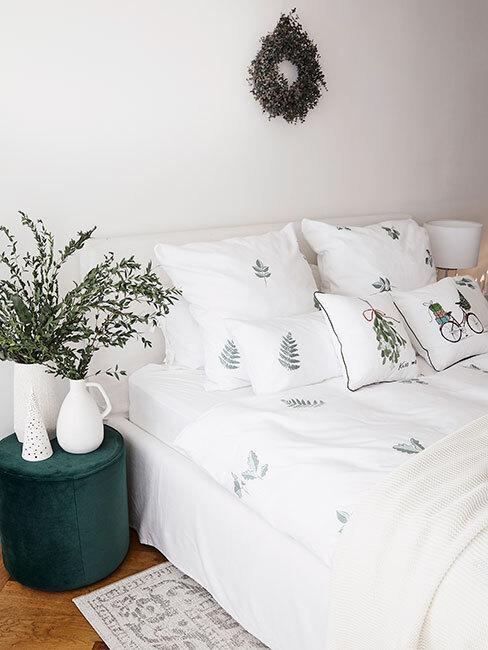 Biała sypialnia z łóżkiem o białej pościeli z choinkami z Westwing Collection obok zielonego pufa