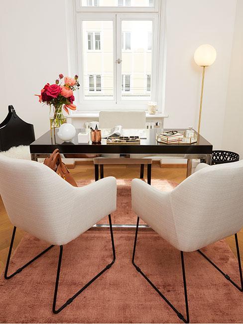 Gabinet w domu z czarnym stołem, białymi krzesłami i dekoracjami w złocie