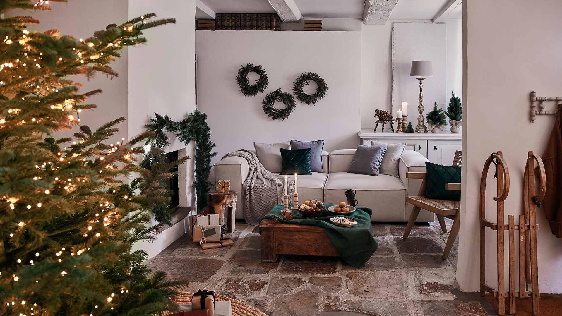 Salon w stylu rustykalnym z białą sofą, udekorowanym stolikiem kawowym, kominkiem z girlandą oraz choinką