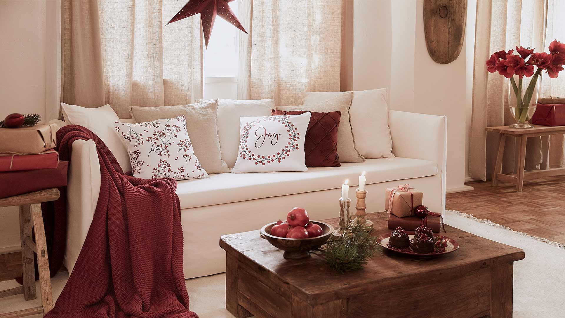 Jasny salon z beżową sofą z białymi i czerwonymi poduszkami, kocem oraz drewnianym stołem z dekoracjami