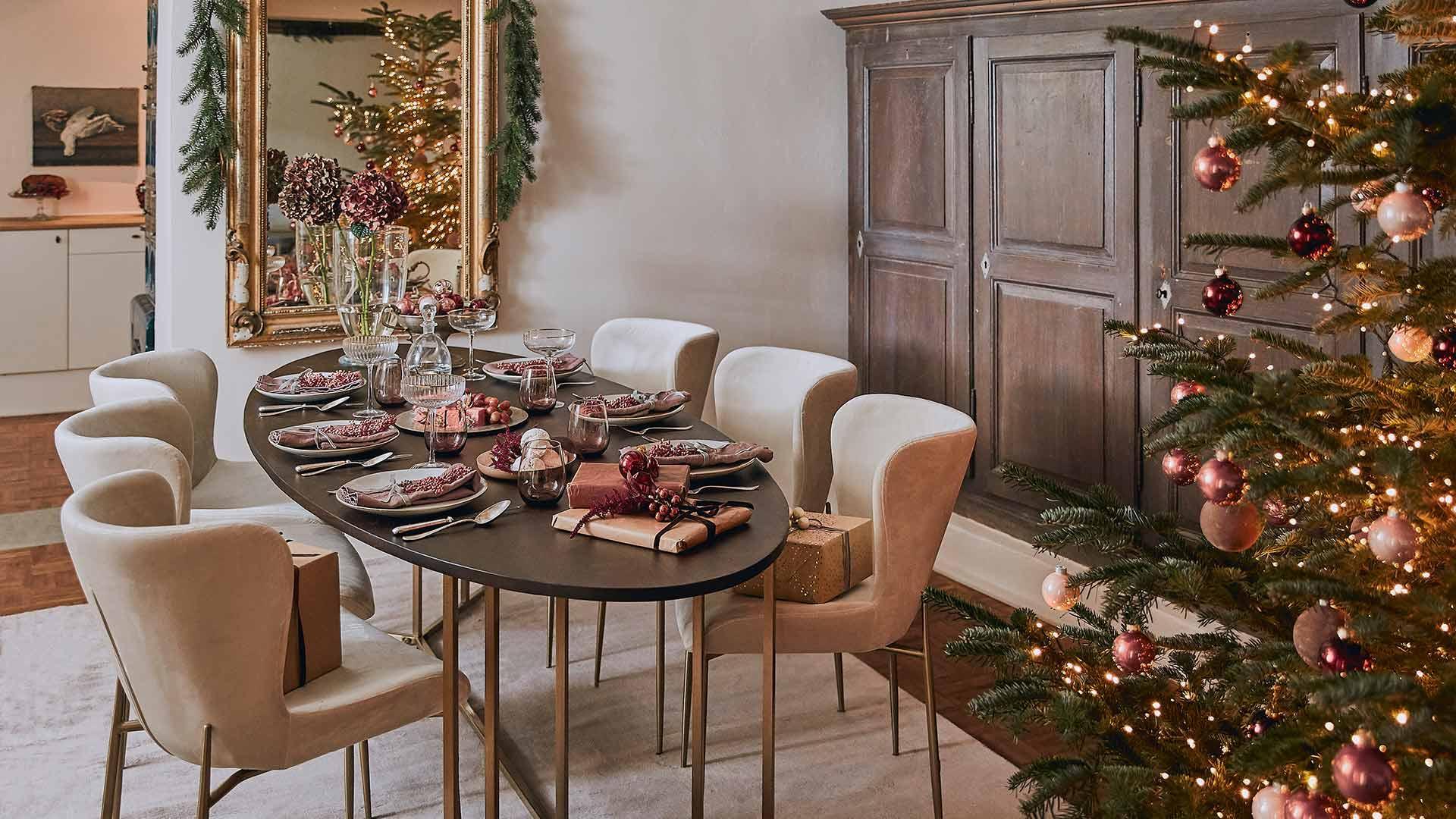 Wnętrze jadalni z drewnianym stołem, beżowymi krzesłami oraz choinką