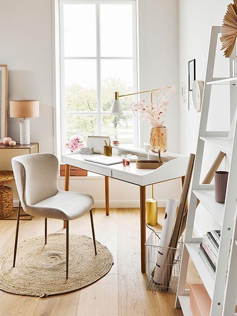 Jasny kącik do pracy przy oknie z białym biurkiem i złotymi dekoracjami
