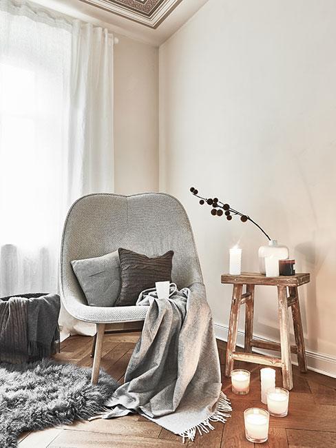 Szyry fotel z pledem otoczony świeczkami