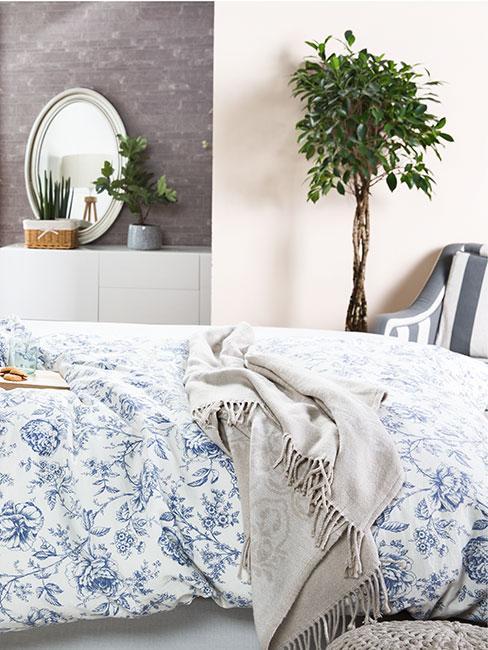 Sypialnia z białą pościelą w niebieskie kwiaty, szarym pledem i drzewem fikusa