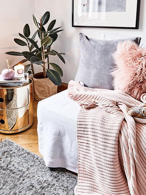 Jasny salon z szarą sofą, różowymi tekstyliami, złotym stolikiem pomocniczym i fikusem