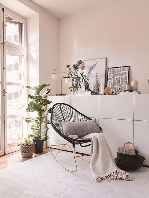 czarny bujany fotel na złotych płozach przy dużym oknie obok białej komody i dużego fikusa