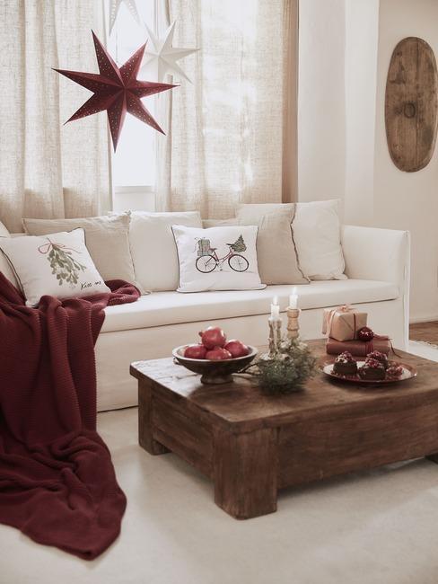 Jasny salon z beżową sofą, na której są poduszki ze świątecznym motywem, czerwonym kocem, drewnianym stolikiem kawowym oraz świątecznymi dekoracjami