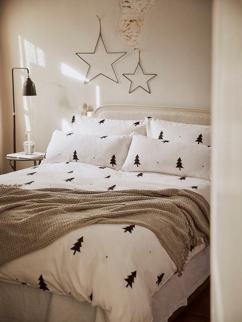 Sypialnia z podwójnym łożkiem o białej, świątecznej pościeli oraz dekoracje w kształcie gwiazdek
