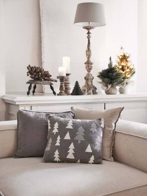Zbliżenie za beżową sofę z trzema poduszkami z motywem świątecznym oraz dekoracjami świątecznymi