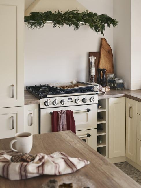 Fragment kuchni z szafkami o beżowych frontach, retro piekarnikiem, wyspą kuchenną o drewnianym blacie oraz świątecznymi dekoracjami