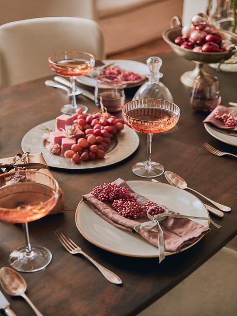 Drewniany, prostokątny stół z białą zastawą, szklanymi kieliszkami z drinkami oraz dekoracjami