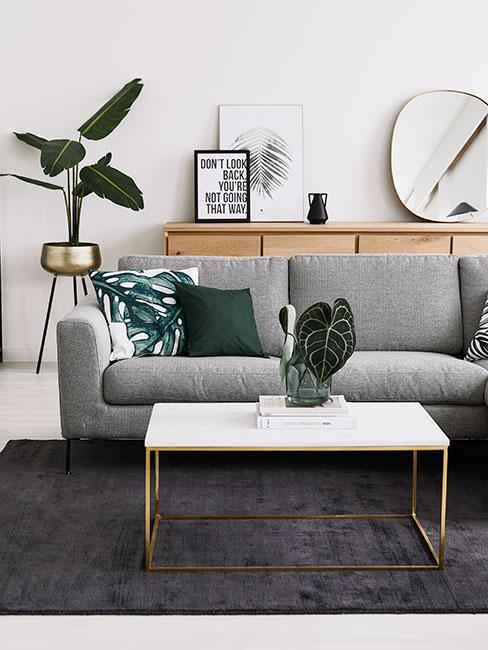 Szara sofa z zielonymi dekoracjami i roślinami
