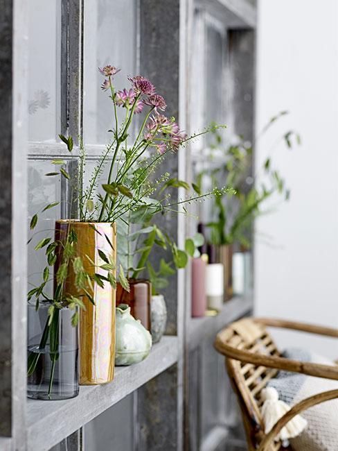 Polne kwiaty w wazonach na regale ściennym