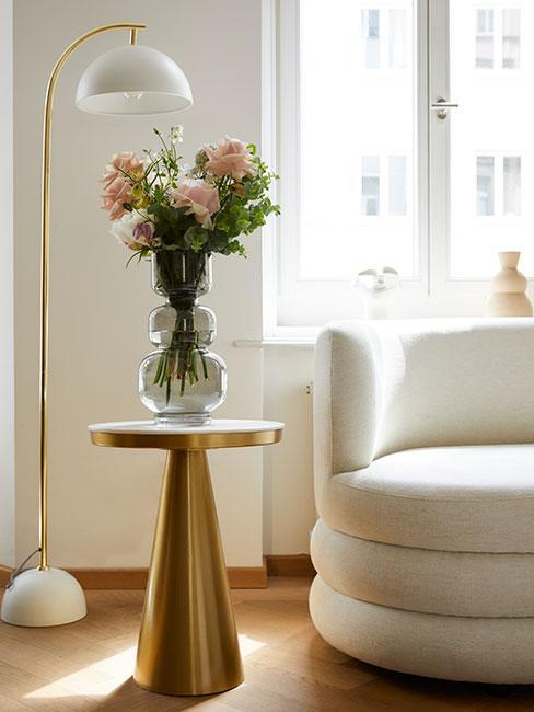 Nowoczesna sofa nerka przy złotym stoliku pomocniczym z białym marmurowym blatem i wazonem z różowymi kwiatami