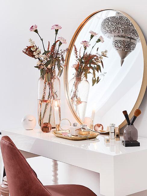 Biała toaletka ze złotym lustrem, różowym krzesłem z aksamitu i wysokim szklanym wazonem z kwiatami