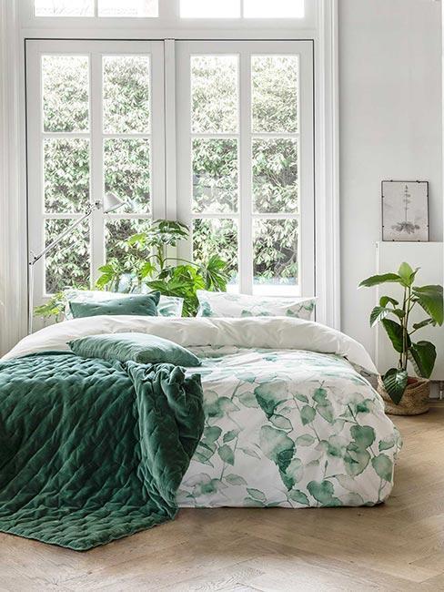 Sypialnia z zielonymi tekstyliami i roślinami