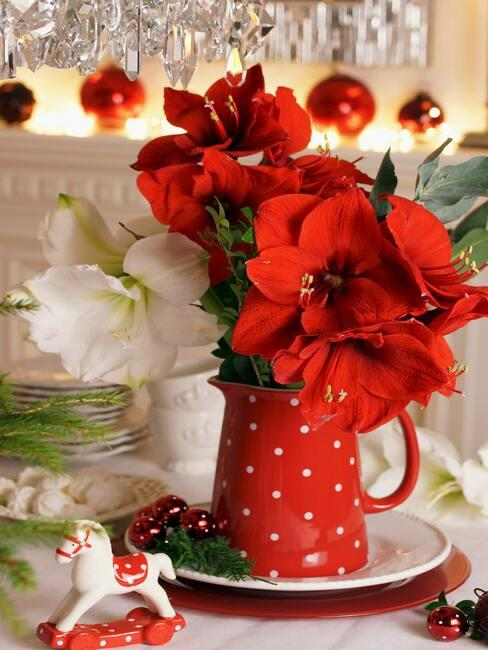 Bukiet z amarylisa w czerwonym dzbanku na stole z białym obrusem