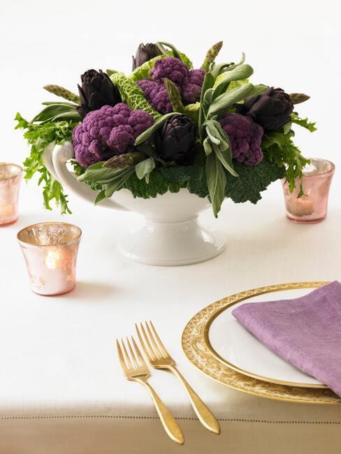 Zimowy bukiet warzywny z fioletowego kalafiora w białym wazonie na stole ze złotą zastawą