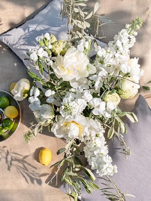 Letni bukiet z białych piwoni na stole z lnianym obruzem oraz złotą tacką z cytrynami i limonkami