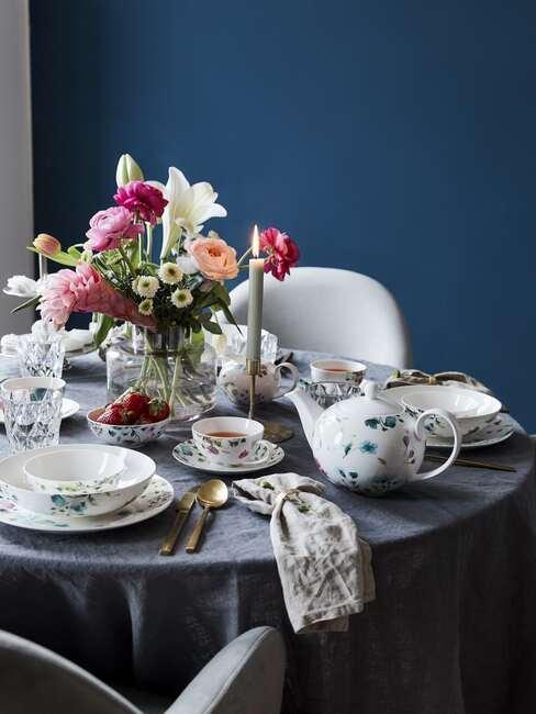 Zastawiony stół białą zastawą we wzory oraz szklany wazon z bukietem z lilii i innych kwiatów