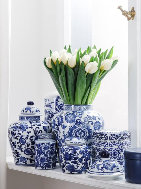 Bukiet białych tulipanów w wazonie ze wzorem z Delftu w otoczeniu podobnej ceramiki