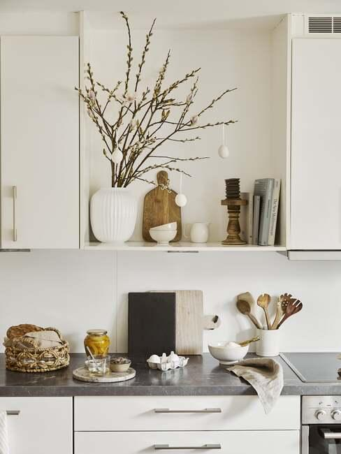 Biała kuchnia z czarnym blatem, białymi frontami szafek oraz półką z wazonem z bukietem gałżek wierzby