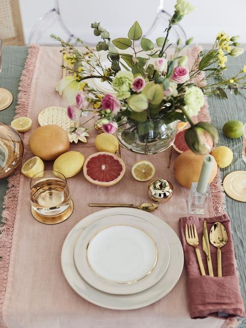 Stół z lnianym obrusem, różowym bieżnikiem, biało - złotą zastawą oraz bukietem kwiatów w wazonie