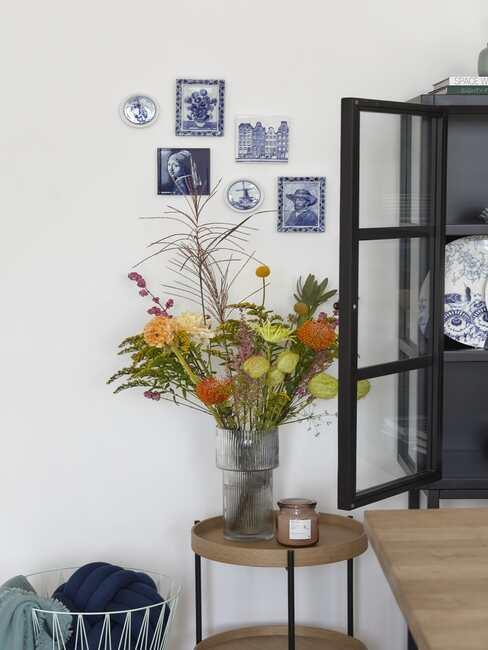 Zbliżenie na drewniany stoliczek pomocniczy z wysokim, niebieskim wazonie z bukietem z dalii w salonie