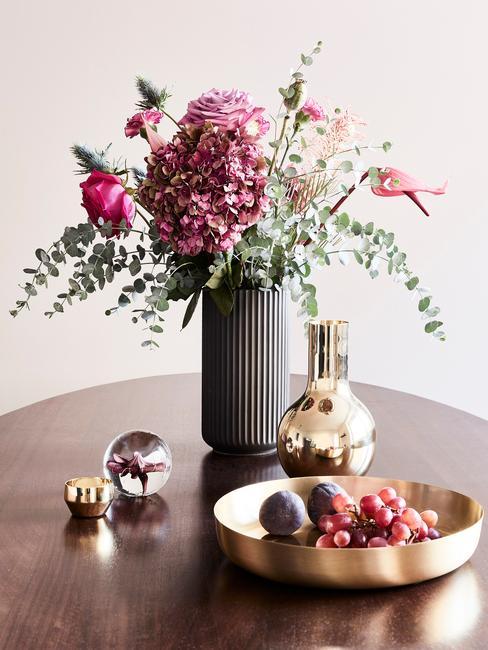 Zbliżenie na buiet z różowych dalii w srebrnym wazonie na drewnianym stole ze złotymi dekoracjami