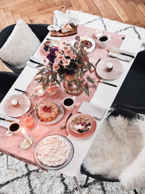 Zastawiony biały, stół z różowym bieżnikiem, talerzami oraz wazonem z bukietem z astrów