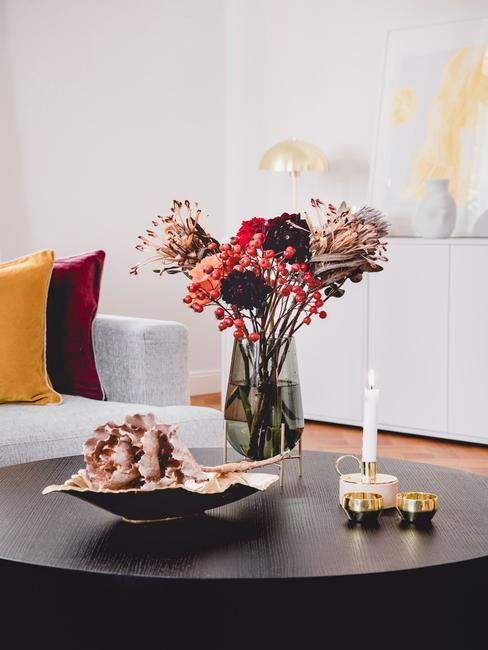 Biała sofa z poduszkami i czarny stolik z dekoracjami i szklanym wazonem z bukietem kwiatów w salonie