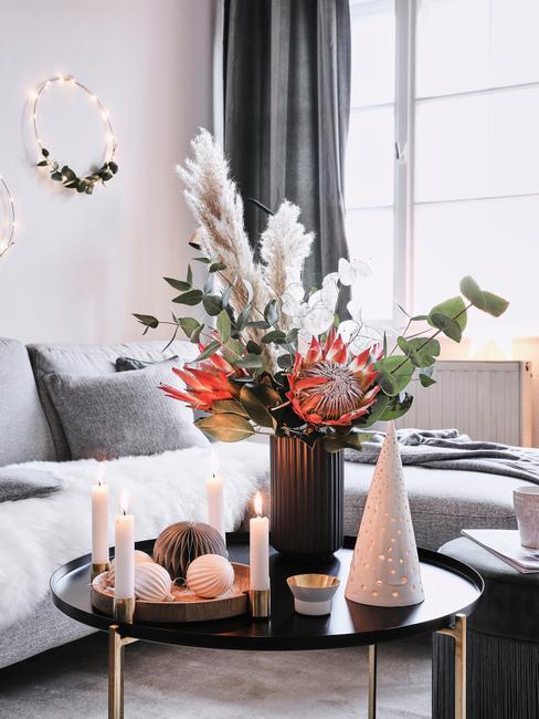Zbliżenie na czarny stolik kawowy z wieńcem adwentowym oraz wazonem z kompozycją z trawy pampawoej, protei i eukaliptusa