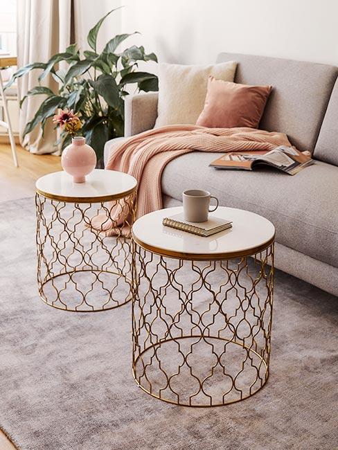 Mały salon z szarą sofą z aksamitu i złotymi ażurowymi stolikami