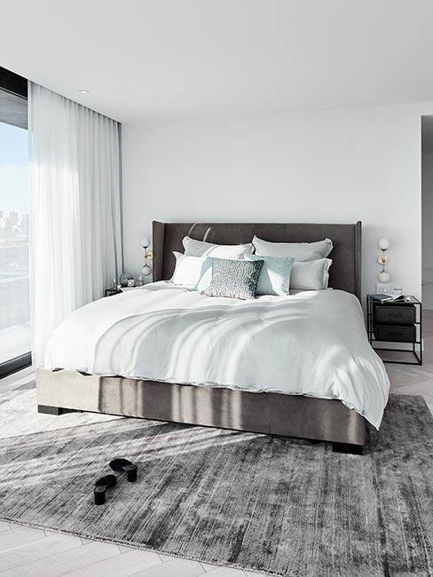 Duże łóżko z szarego aksamitu w jasnej sypialni z szarym dywanem