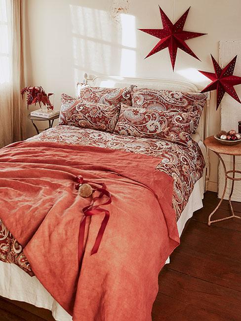 Sypialnia udekorowana na święta z wzorzystą czerwoną pościelą i czerwonymi gwiazdami