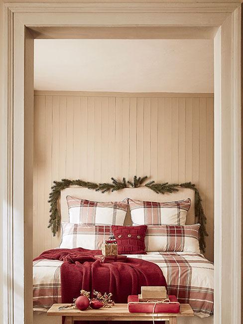 Sypialnia udekorowana na święta z pościelą w kratę i gałązkami świerku nad wezgłowiem