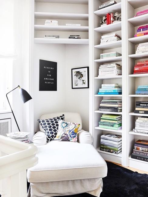 Kącik do czytania z białym szezlongiem i białym regałem na książki ustawione kolorystycznie
