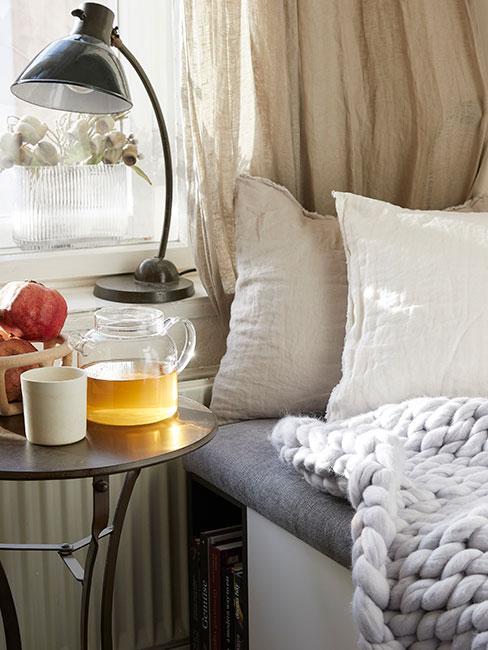 Przytulny kącik do picia herbaty przy oknie z jasnymi tekstyliami