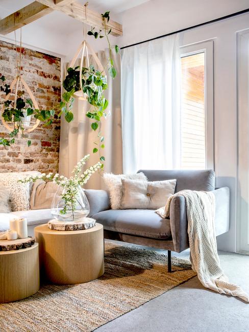 Fragment salonu scandi z szarym fotelem z kocem, drewnianymi stoliczkami z roślinami oraz wiszącymi donicami