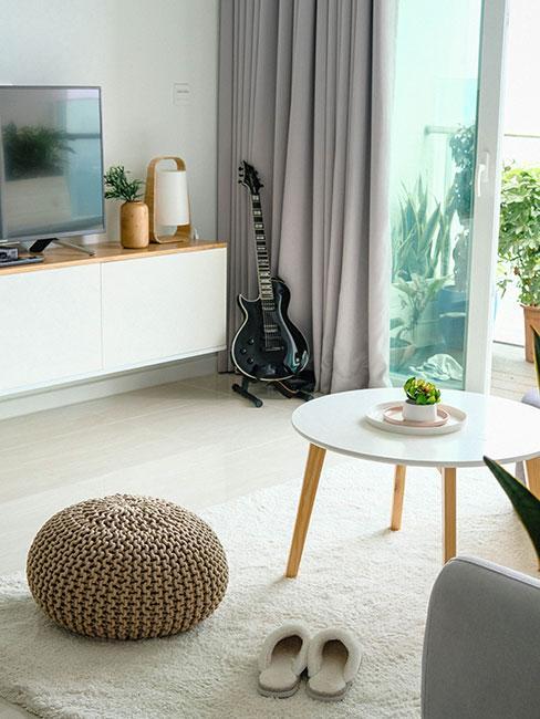 jasny salon w stylu skandynawskim z pufą z dzianiny, białym drewnianym stolikiem i balkonem