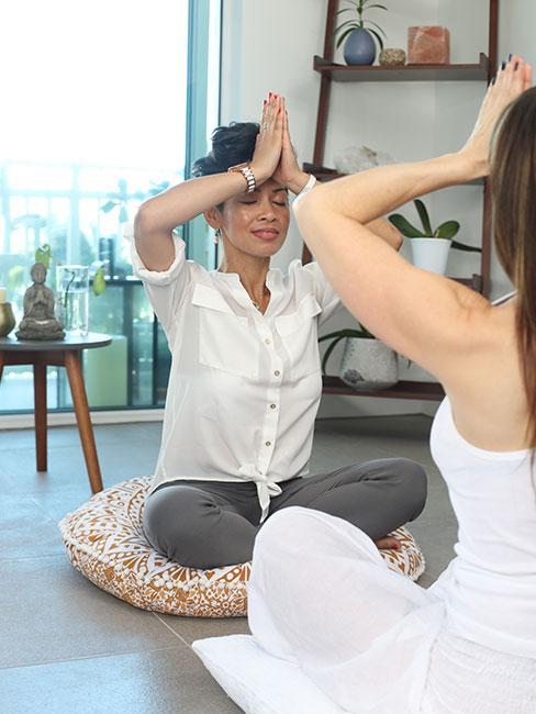 Dwie kobiety medytujaące naprzeciw siebie w pozycji lotosu