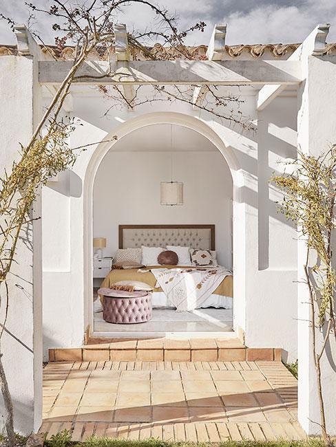 Jasna sypialnia w stylu śródziemnomorskim z dużym wyjściem na taras