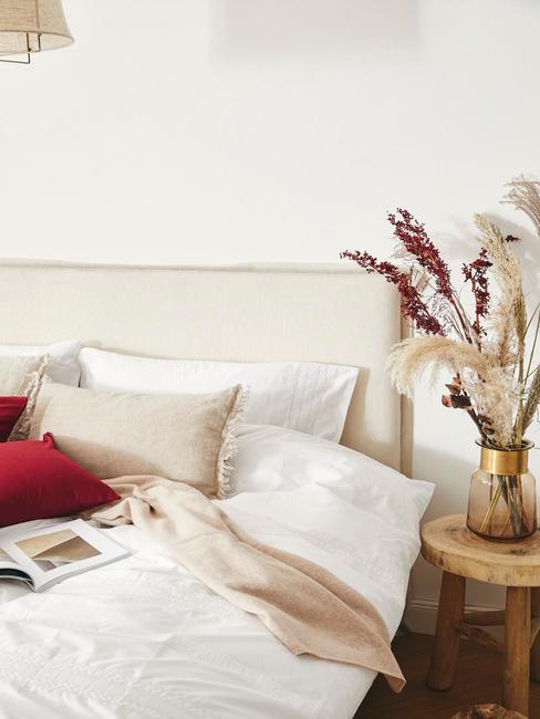 Zbliżenie na łóżko z białym zagłówkiem i kolorowymi poduszkami oraz stolik nocny z wazonem kwiatów