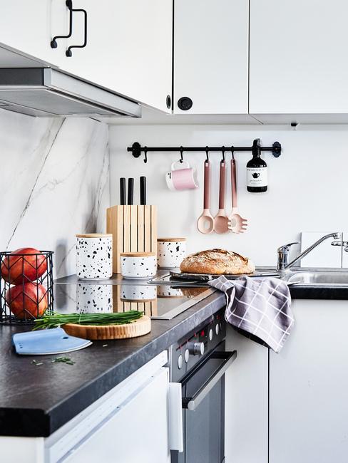 Biała kuchnia w stylu scandi z białymi szafkami, czarnym blatem oraz dodatkami