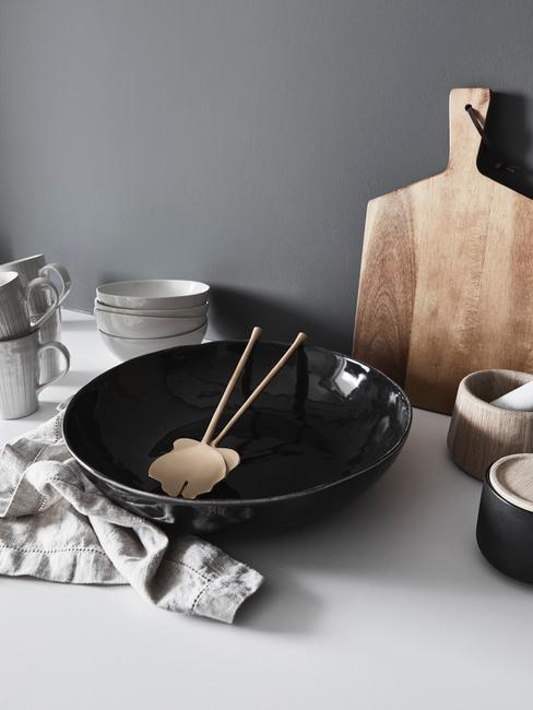 Zbliżenie na zastawę stołową w czarnym kolorze, drewnianą deskę do krojenia oraz pojemniki