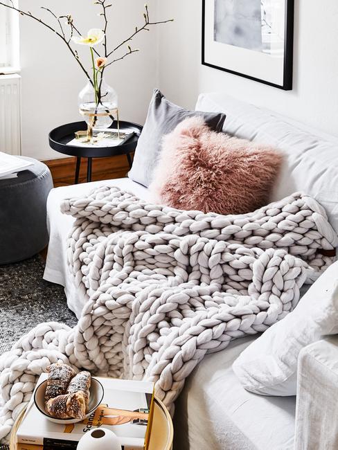 Zbliżenie na sofę z szarnym, gruboplecionym kocem, poduszkami oraz czarny puf w salonie skandi