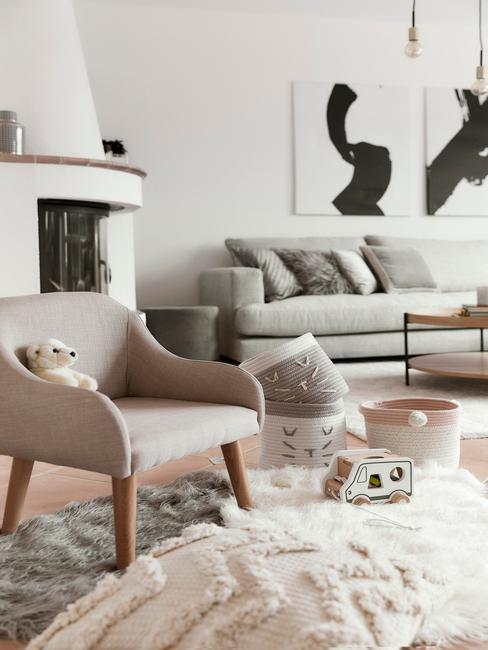 Rodzinny salon skandynawski w bieli, z szarą sofą, beżowym krzesłem, dywanem oraz kominkiem